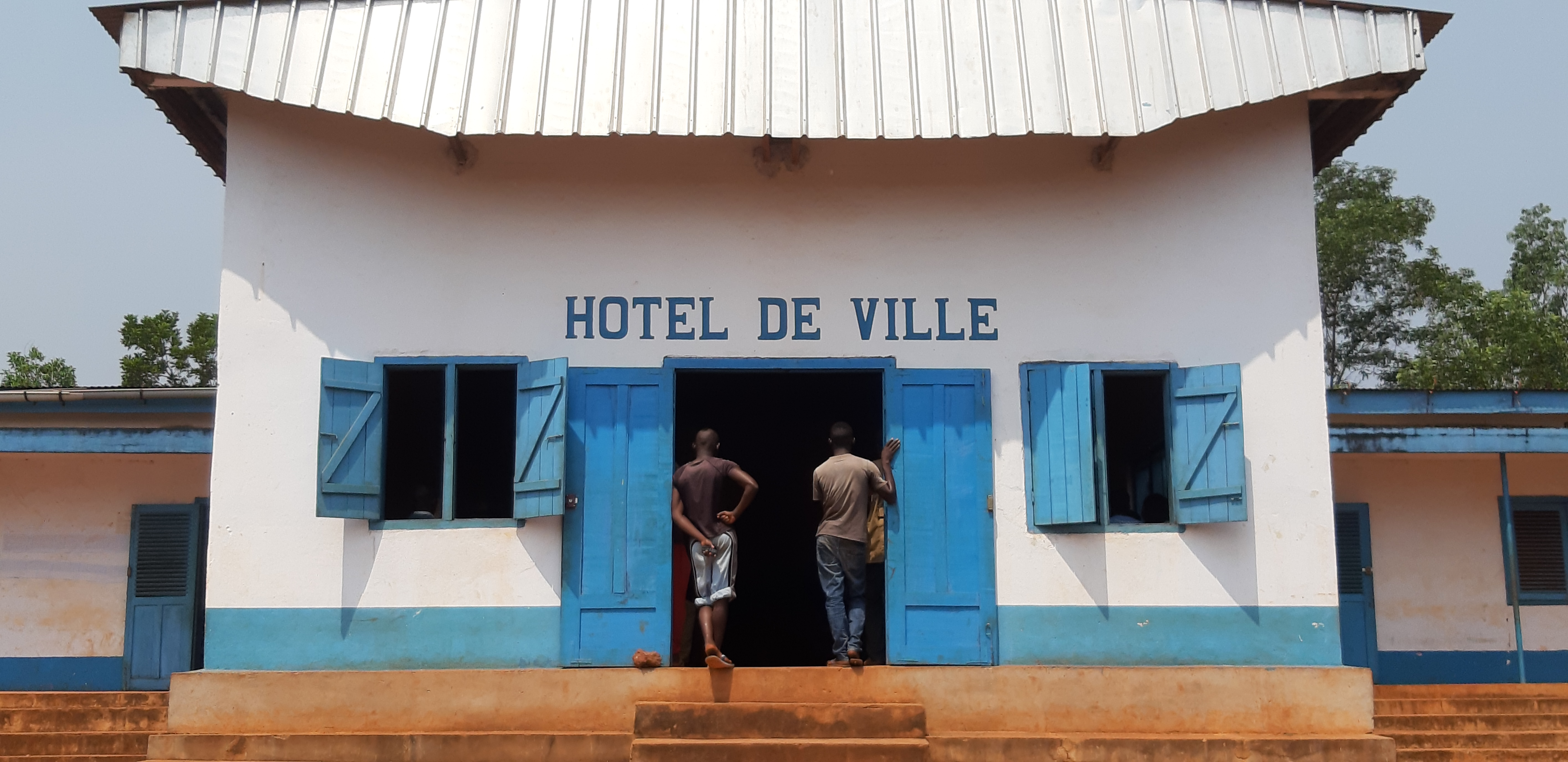 Two men stand in front of the Hotel De Ville in the Central African Republic