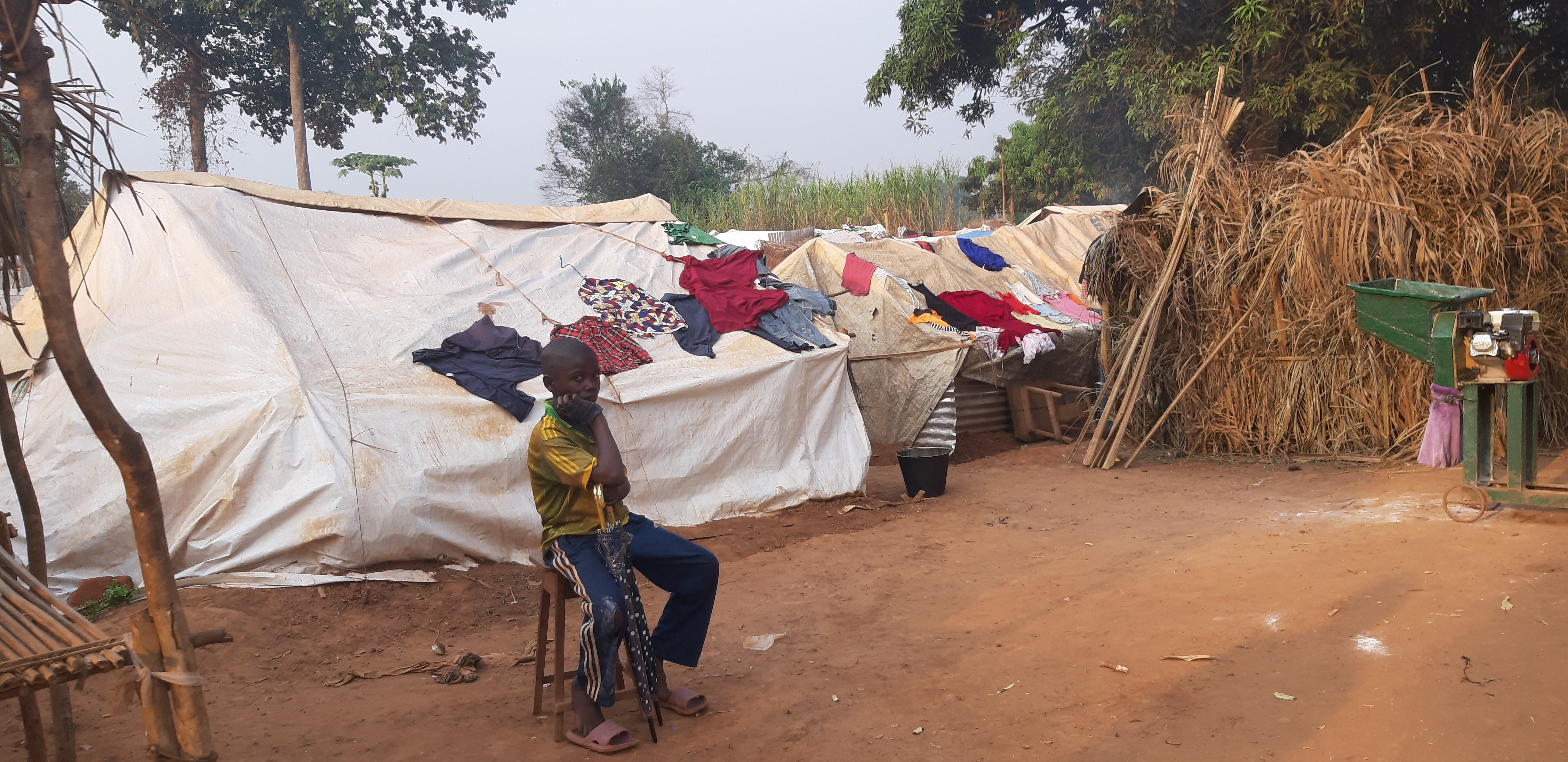 Boy sits in front of tents in camp in Central African Republic