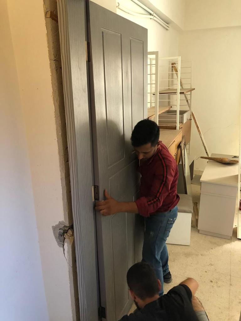 Two men from the KAICIID Be Beirut project install a door