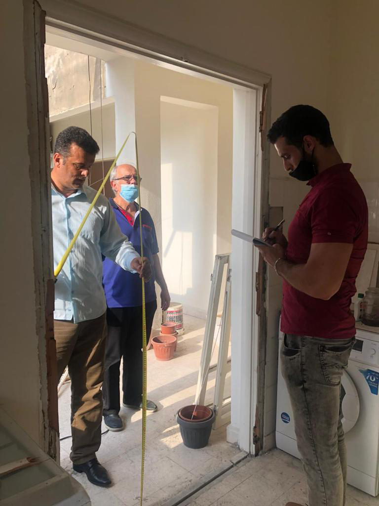 Three men from the KAICIID Be Beirut project measure a space for a door