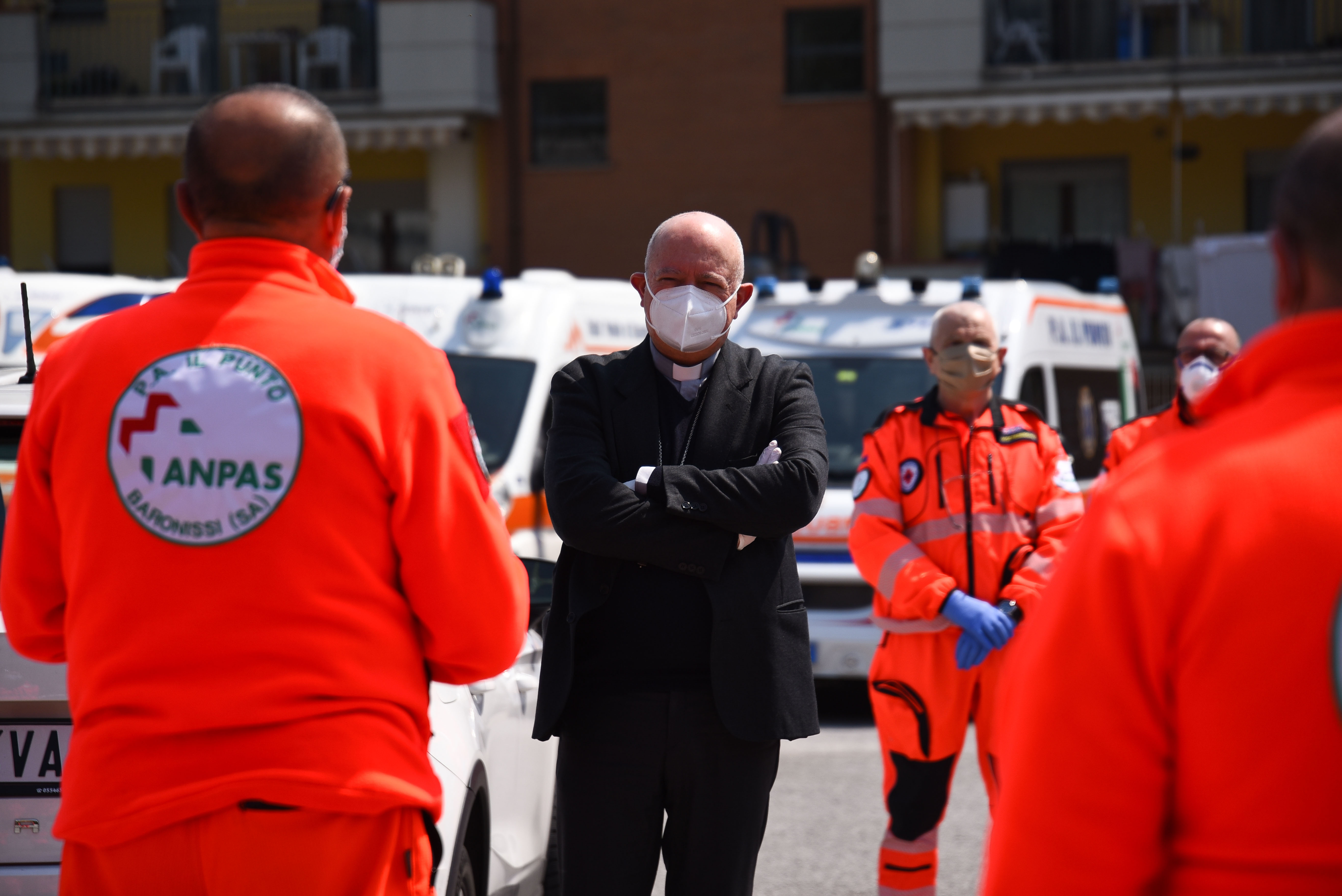 A priest stands next to emergency frontline health workers
