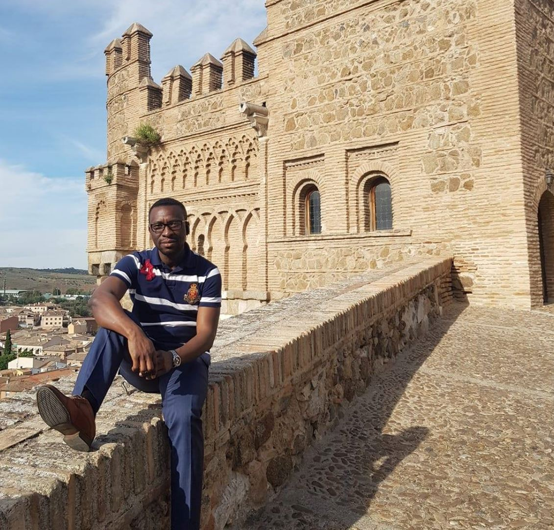KAICIID Fellow Johnson Amamnsunu sits on a wall in Spain