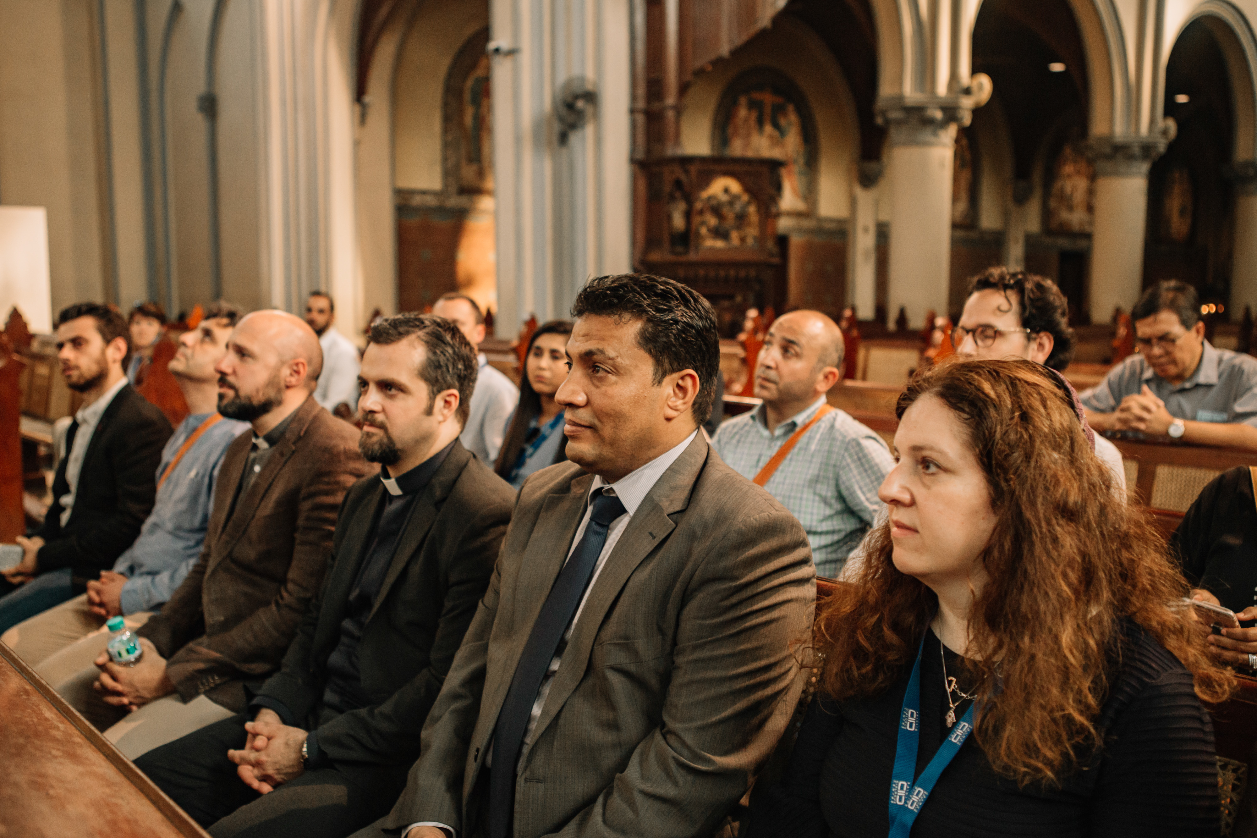 A group of KAICIID Fellows sit together in a cathedral
