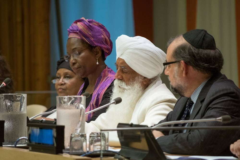 Four religious leaders sit together at table