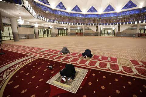 رجال دين مسلمون يمارسون التباعد الجسدي في أثناء أداء صلاتهم