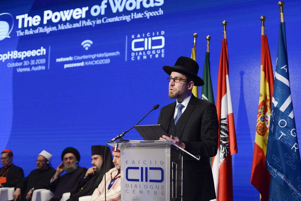 Rabbi Hofmeister stands at podium at KAICIID Power of Words Conference. Behind him sit 5 religious leaders.