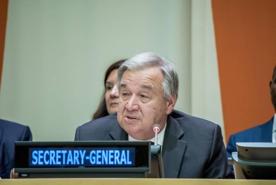 UN Secretary General Guterres sits at table