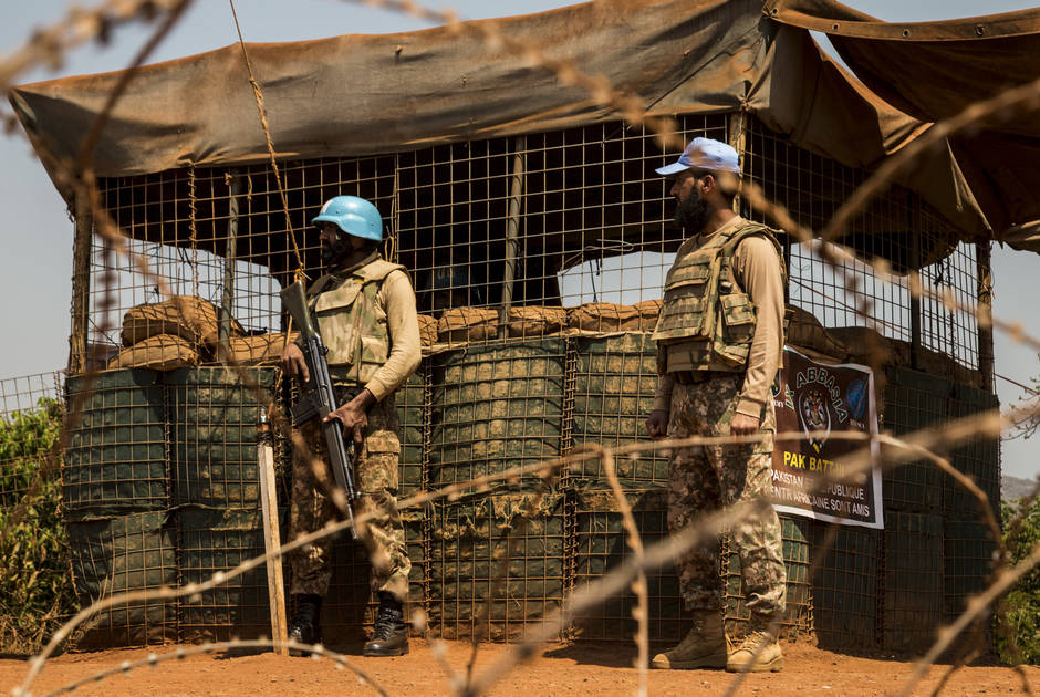 Two UN Peacekeepers stand behind barbed wire