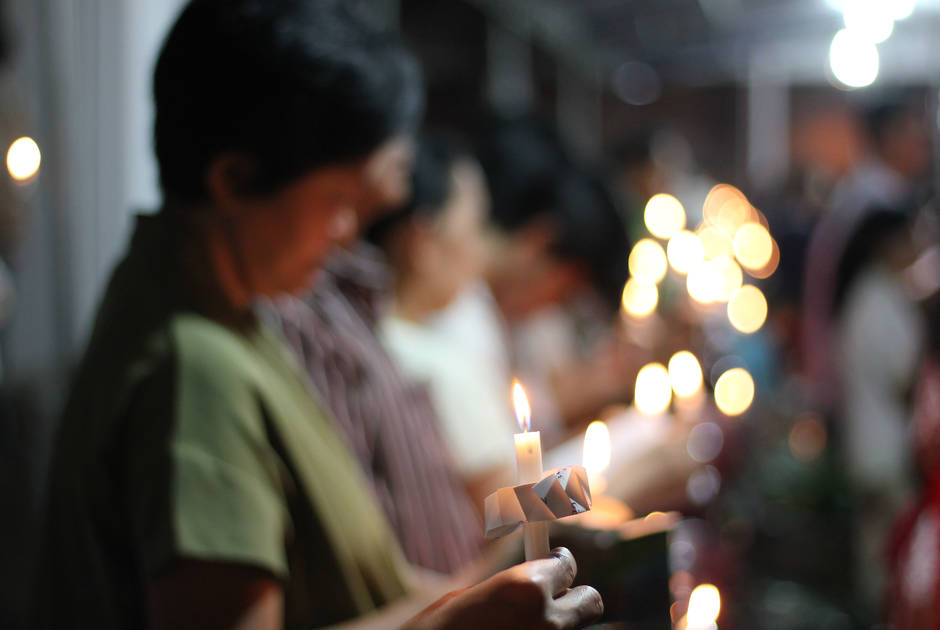Women hold candles at a worship service in Indonesia