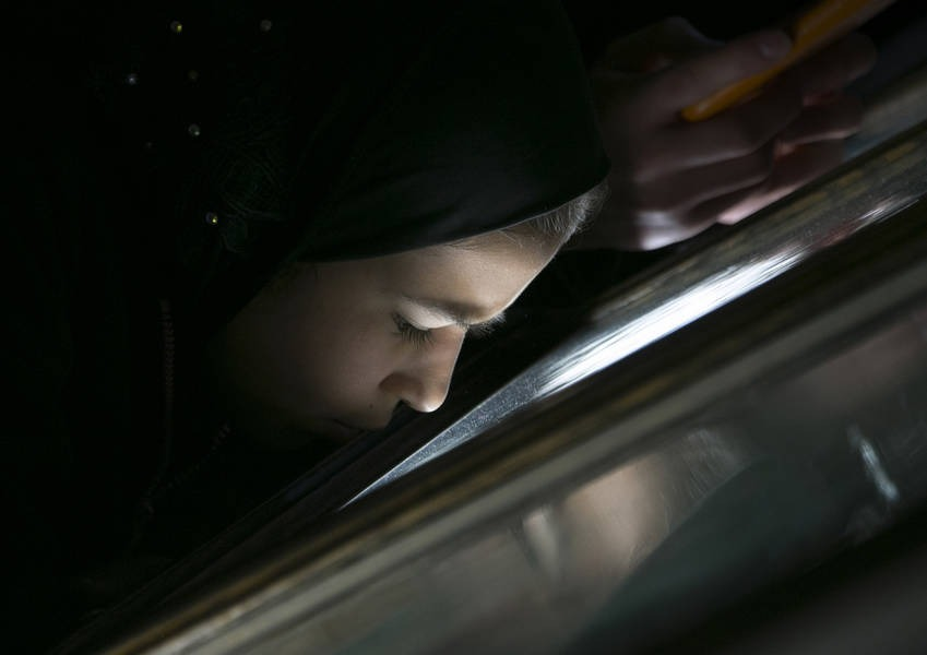 A young asylum seeker peers into a display case in a museum.