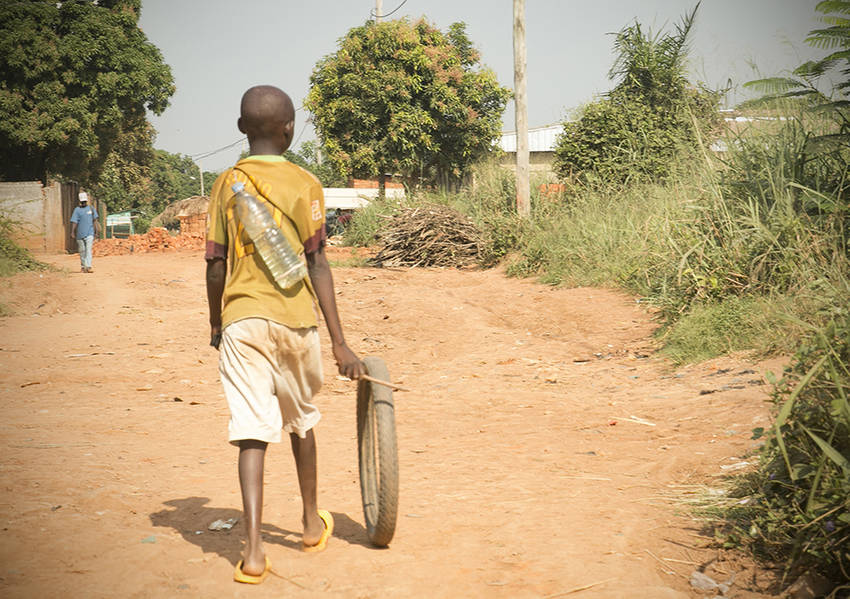 A child rolls a discarded tire in the late morning sun. Photo: Kaleb Warnock/KAICIID