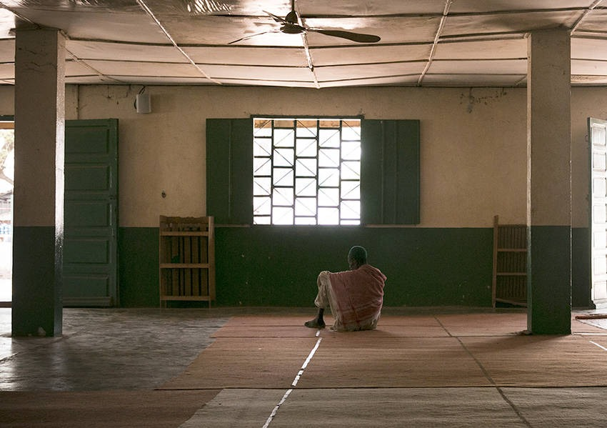 A man sits alone, enveloped in the stillness of the Central Mosque located in PK5. Photo: Kaleb Warnock/KAICIID