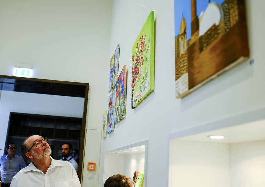 A visitor examines the paintings.